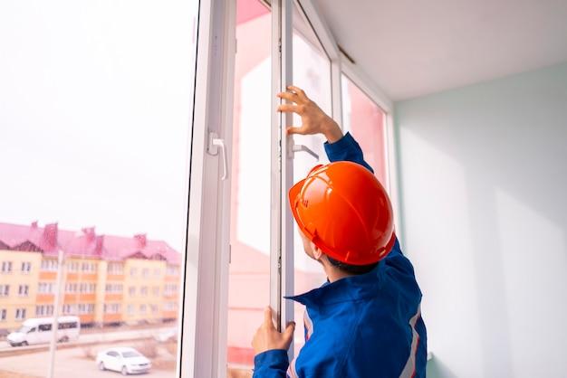 전문 핸디 작업자가 집에 창을 설치하고 조정합니다.