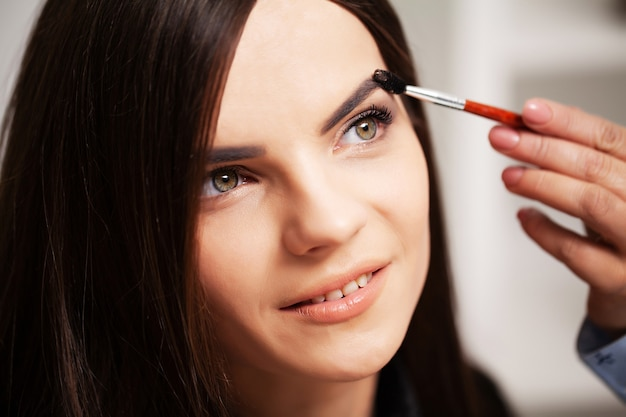 Вечерний макияж молодой женщине делает профессиональный визажист.