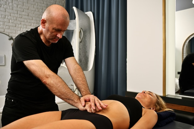 Профессиональный массажист делает антицеллюлитный массаж женщине, которая лежит на массажном столе и получает лечебный массаж по уходу за телом.