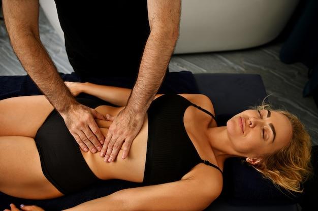 Профессиональный массажист в оздоровительном спа-центре проводит антицеллюлитный массаж женщине, лежащей на массажном столе.