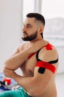 プロの理学療法士が患者の腕と肩に伸縮性のある運動学テープをテーピングします。