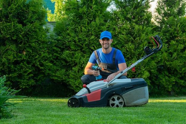 Профессиональный ремонтник ремонтирует газонокосилку мужчина ремонтирует газонокосилку на своем заднем дворе.