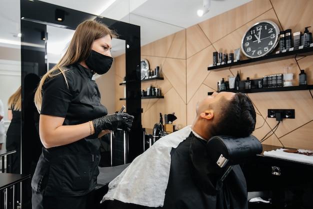 モダンでスタイリッシュな理髪店のプロのスタイリストが若い男の髪を剃り、カットします。ビューティーサロン、ヘアサロン。