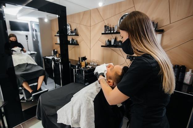モダンでスタイリッシュな理髪店のプロのスタイリストが若い男の髪を剃り、カットします。