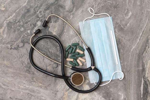 Защитная синяя маска и витамины, фонендоскоп лежат на сером мраморном столе. концепция сохранения здоровья.