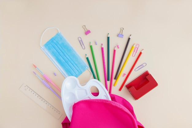 ピンクのバックパックから散らばった保護医療マスクと学校と事務用品。