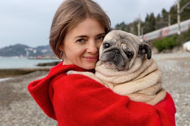 赤いコートを着た女性の腕の中のパグ。海沿いの暖かい冬の日。