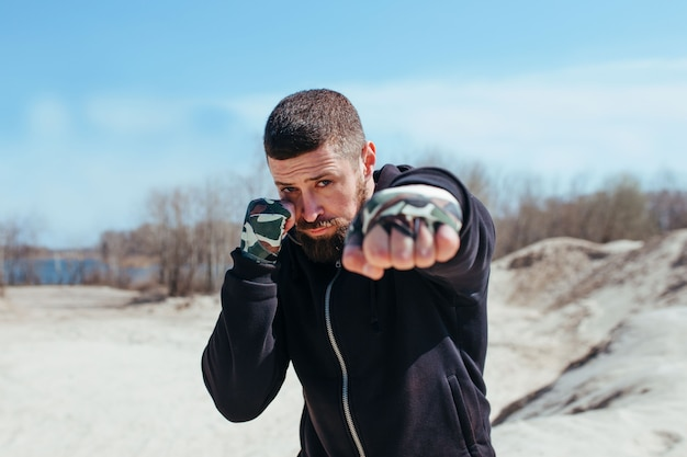 ポンプアップされたボクサーが砂の上を走り、拳を前景に