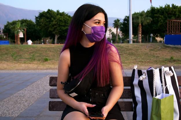 쇼핑 가방과 함께 보라색 머리 여자입니다. 그녀는 바이러스 전염병 때문에 얼굴에 보라색 마스크를 쓰고