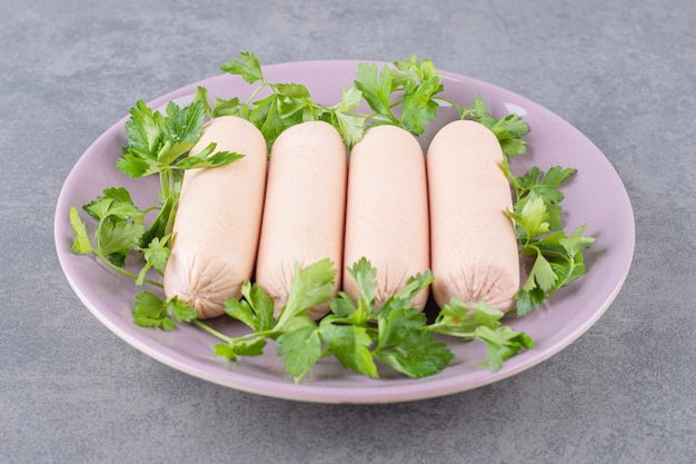 パセリと茹でたソーセージの紫色のプレート。