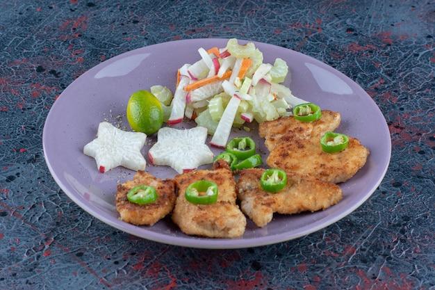 칠리 페 퍼와 치킨 너겟의 보라색 접시.
