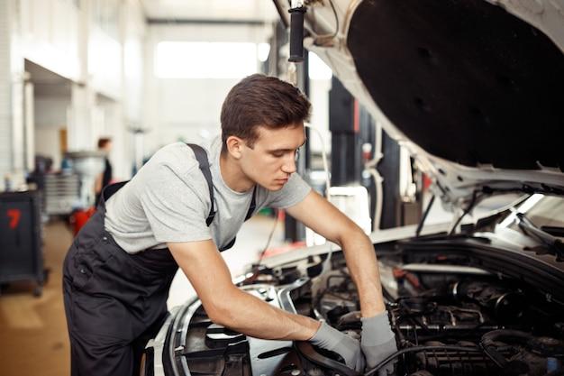 Квалифицированный автомеханик ремонтирует автомобиль в автосервисе.