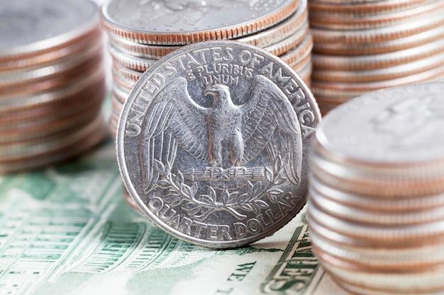 Четверть доллара сша стоит на краю возле кучи американских монет, фото крупным планом