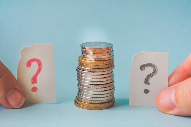 Знак вопроса и стопка монет. концепция финансового кризиса.