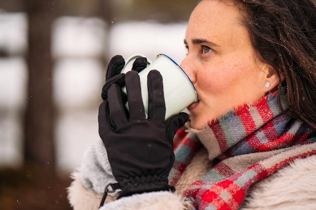 Тихая женщина, одетая в пальто, пьет кофе - концепция отпуска - крупный план