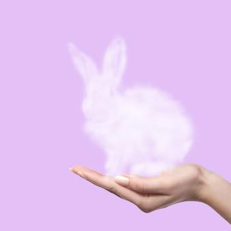 ピンクの背景に女性が雲でできたうさぎを手に持っています。イースターのコンセプト。休日の贈り物として