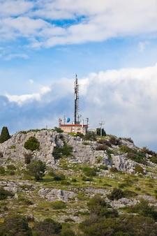Башня радиосвязи с тарелками на холме на фоне голубого неба.