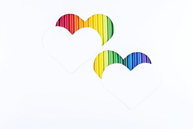 Радуга карандашей в двух вырезанных сердечках под двумя белыми сердечками на фоне белой бумаги.