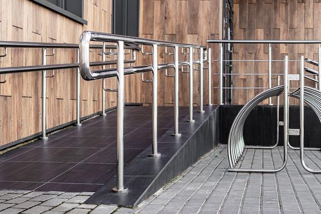 Пандус и металлические перила у входа в жилой дом для удобства инвалидов и пожилых людей.