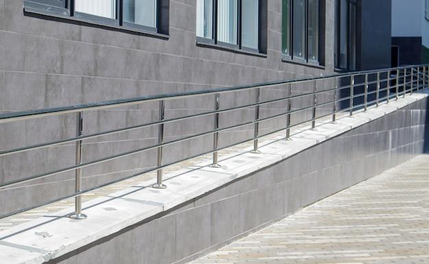 건물 앞에 어린이를 동반한 휠체어, 자전거 및 유모차를 위한 스테인리스 스틸 난간이 있는 경사로. 휠체어를 들어올리기 위한 난간. 반짝이는 스테인리스 스틸 난간.