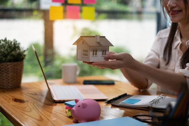 부동산 중개인이 주택 보험 구매에 관심이 있는 고객에게 주택 모델을 보여줍니다. 주택 보험 및 재산의 개념입니다.