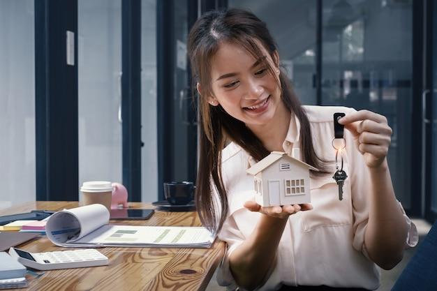 부동산 중개인이 주택 보험 구매에 관심이 있는 고객에게 주택 모델을 보여줍니다. 집이나 자동차 보험과 재산의 개념.