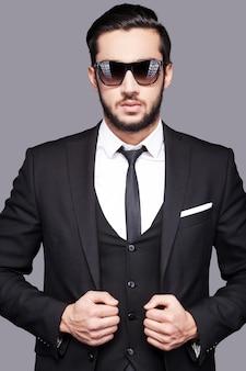 本物の男。灰色の背景に立っている間彼のジャケットに手をつないで正装でハンサムな若い男の肖像画