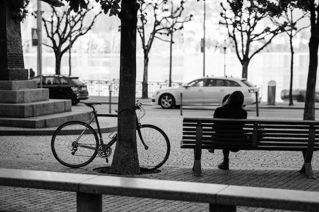 自転車を近くに置いてベンチに座っている女性の背面図。