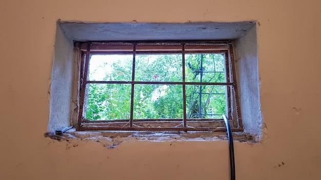 직사각형 지하실 창은 금속 메쉬와 그릴로 조입니다. 오래 된 회색 건물의 벽에 기술 창.