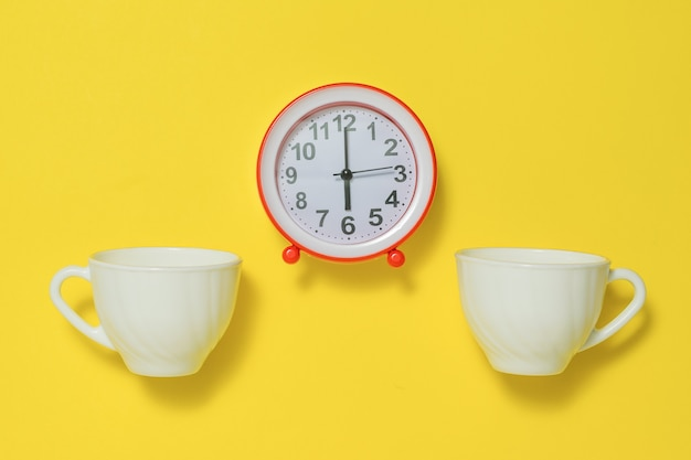 노란색 배경에 손잡이가 있는 빨간색 알람 시계와 두 개의 커피 컵. 아침에 톤을 들어 올리는 개념. 플랫 레이.