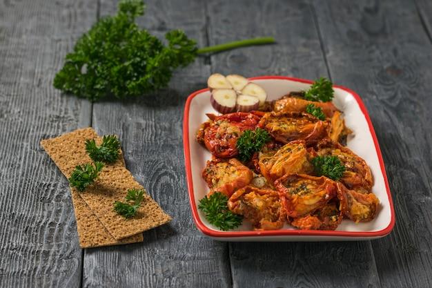 Красно-белая тарелка вяленых помидоров на деревянном столе. средиземноморская закуска из томатов. вегетарианская пища.