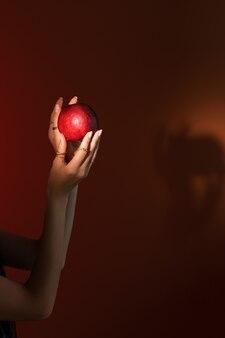 빨간 배경 클로즈업 할로윈에 여자의 손에 빨간 사과