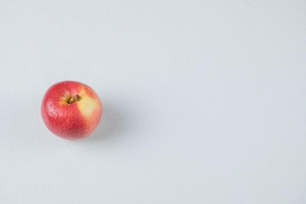 白で隔離される赤いリンゴ。