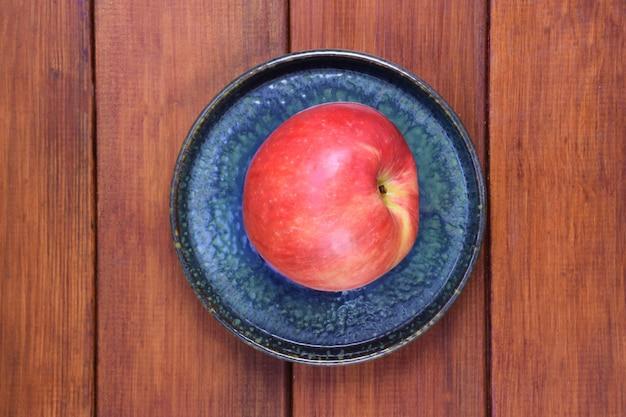 Красное яблоко лежит на керамическом блюдце на деревянном фоне в центре кадра.