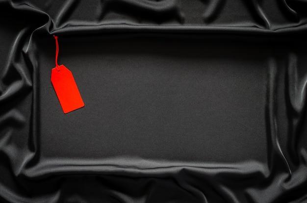 テキスト用のスペースがある黒い滑らかで波状の布に赤い空白の値札。ブラックフライデーのコンセプト。