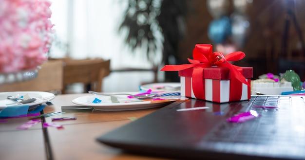テーブルの上のラップトップの近くに、色付きの紙吹雪の赤いボックスが立っています。誕生日のお祝いのコンセプト。