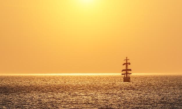 범선의 실루엣과 붉은 불타는 석양. 선원들은 배의 돛대에 돛을 달았습니다. 바다에 떠있는 흰색 범선. 공간을 복사하십시오.