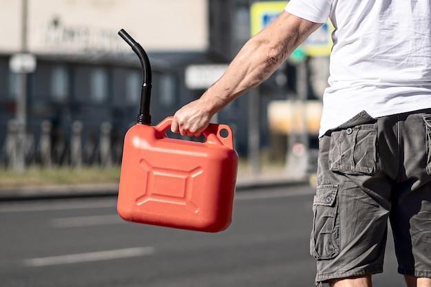 차 근처 아스팔트에 빨간 용기. 차는 기름이 다 떨어져 멈췄다. 도로에서 다른 운전자의 도움을 바라는 청년.
