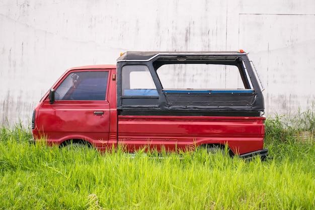 Красная машина припаркована на лугу