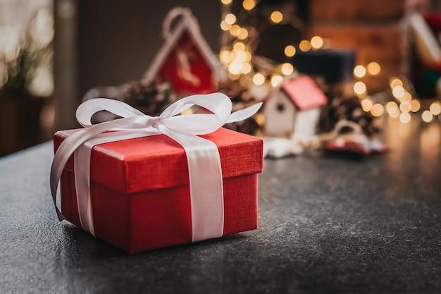 Красная рождественская подарочная коробка с белой лентой лежит на столе