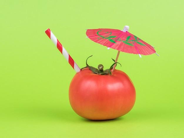 Красный зонтик для коктейля и красная трубка в помидоре на зеленом фоне.