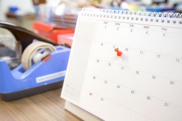 Штырь красного цвета на календаре, концепция для плановика событий.