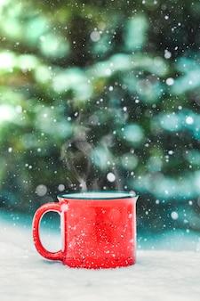 Красная чашка с горячим зимним напитком (глинтвейн, какао, кофе, чай) на фоне зимнего леса и снега. зимнее настроение и комфорт.