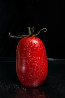 Красный, свежий, спелый, сочный помидор с зелеными листьями и каплями воды на темном фоне.