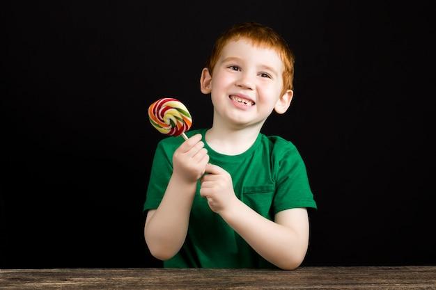 아름다운 얼굴을 가진 빨간 머리 소년이 막대기에 달콤한 다색 사탕을 먹고, 설탕으로 만든 롤리팝을 가진 소년