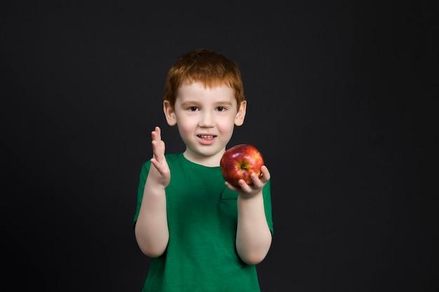 아름다운 얼굴의 빨간 머리 소년이 떨어 뜨려 손상된 사과를 연구합니다.