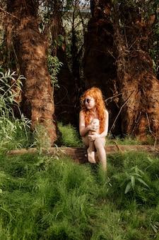 Рыжая девушка в купальнике задумчиво сидит среди зелени леса.