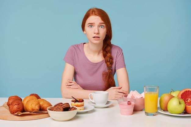 赤毛の少女は、腕を組んでテーブルに座って、前にクロワッサンを焼いておびえています。