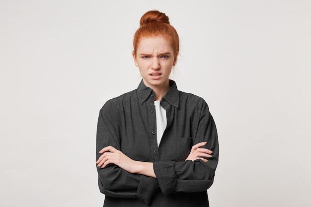 腕を組んで立っているお団子に髪を折りたたんだ赤毛の女の子はうんざりしている