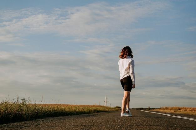夏の晴れた日、白いシャツを着た赤い髪の女性が畑の間の道を歩いています。町からの旅